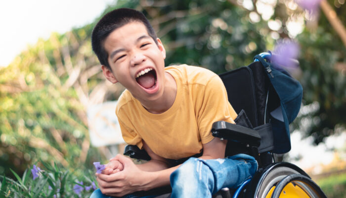 Disabled child on wheelchair is playing, learning and exercise in the outdoor city park like other people,Lifestyle of special child,Life in the education age of children,Happy disability kid concept.